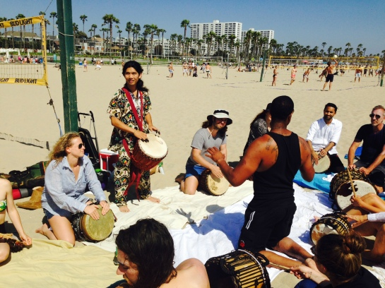 Team drum circle on the beach.